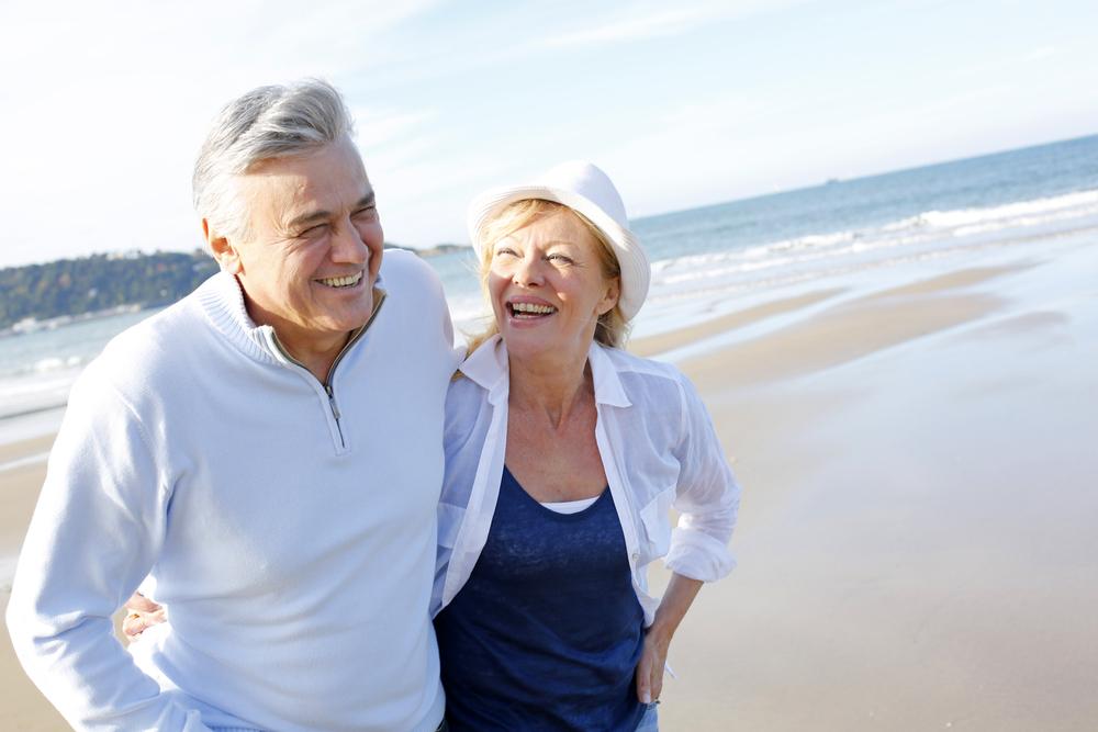 married couple walks on the beach